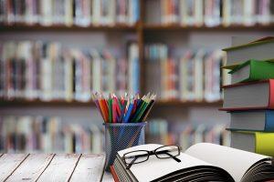 pila-de-libros-con-gafas-en-escritorio-de-madera_1134-17